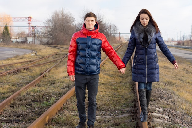 Coppia facendo una tranquilla passeggiata lungo le linee ferroviarie tenendosi per mano mentre la giovane donna si equilibra sul binario di metallo