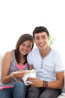 Coppie degli adolescenti che mangiano pasta con copia-spazio