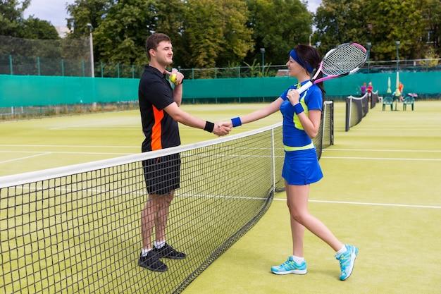 Coppia di giocatori di tennis che agitano le mani sopra la rete che indossa un abbigliamento sportivo su un campo all'aperto in estate o in primavera