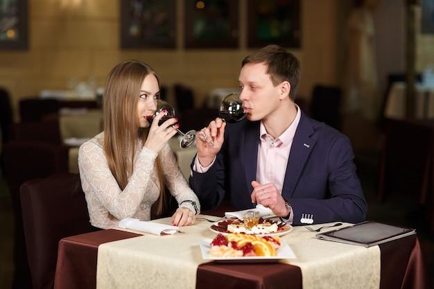Coppie che tostano i bicchieri di vino in un ristorante di lusso