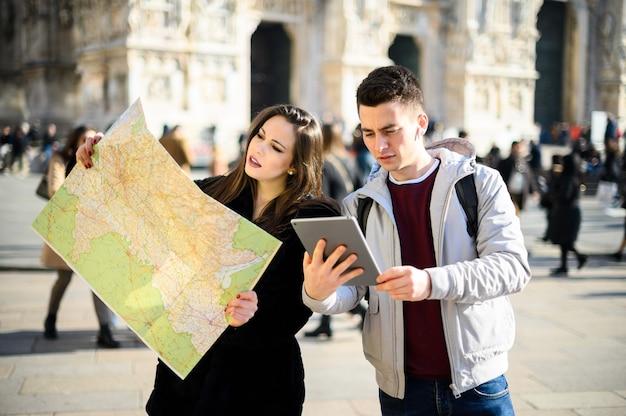 Coppia di turisti in città guardando una mappa e discutendo sulla prossima destinazione