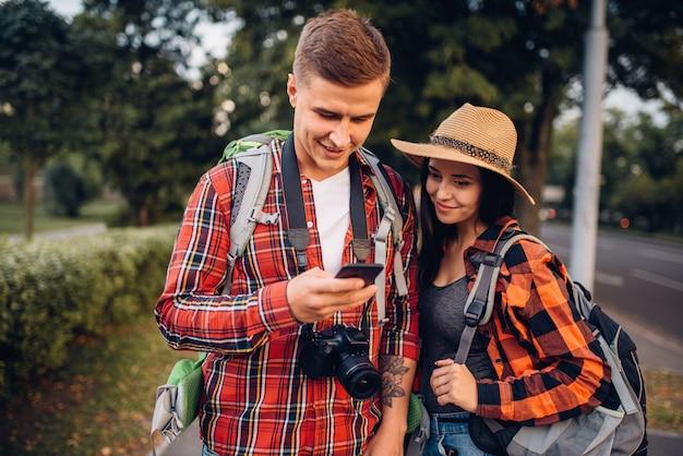 Coppia di turisti in cerca di attrazioni della città sul navigatore, escursione in città. escursioni estive. escursione all'avventura di un giovane uomo e una donna