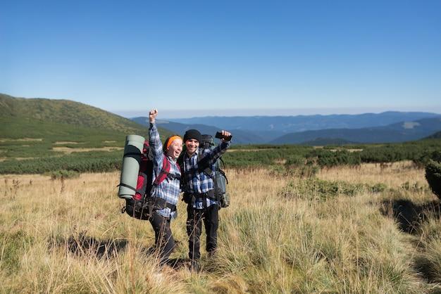 Una coppia di turisti innamorati, un uomo e una donna in piedi su una pianura di montagna alzano le mani e gridano allegramente