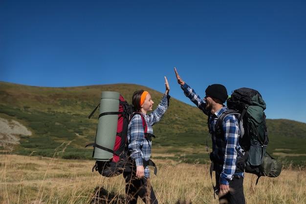 Una coppia di turisti innamorati, un uomo e una donna in piedi su una pianura di montagna alzano le mani