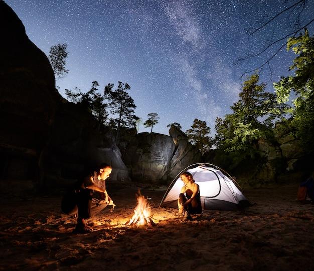Coppia i turisti che riposano accanto al campo, tenda del fuoco di notte
