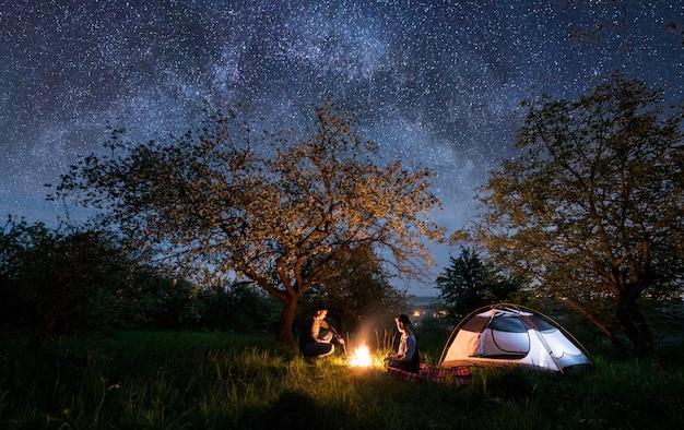 Coppia i turisti seduti a un falò vicino alla tenda sotto gli alberi e il bellissimo cielo notturno pieno di stelle e via lattea. notte in campeggio