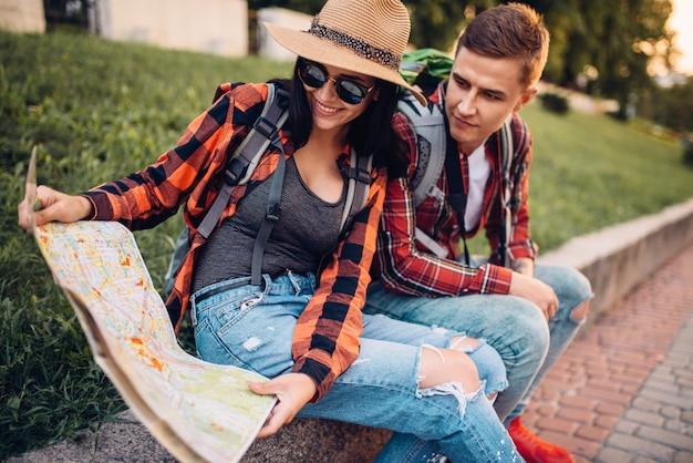 Coppia di turisti studia la mappa delle attrazioni, escursione in città. escursioni estive. escursione all'avventura di un giovane uomo e una donna