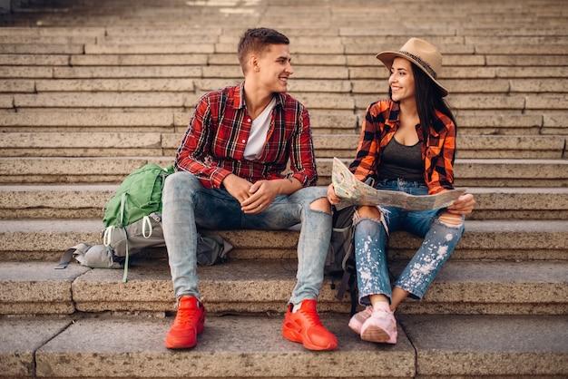 Coppia di turisti con zaini in appoggio sui gradini di pietra, escursione in paese. escursioni estive. escursione avventura di giovane uomo e donna, passeggiate in città