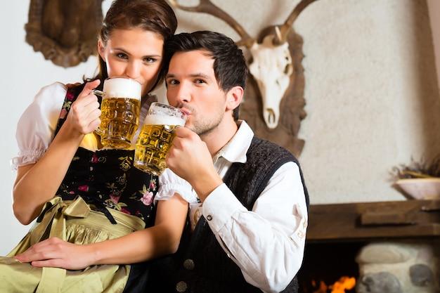 Coppia in una baita di montagna tradizionale con camino a bere birra