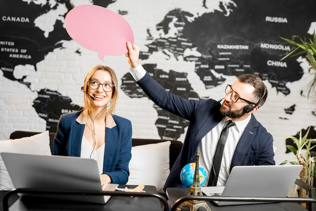 Coppia di travel manager che sognano con bolle colorate sopra la testa seduti nell'ufficio dell'agenzia con la mappa del mondo sullo sfondo