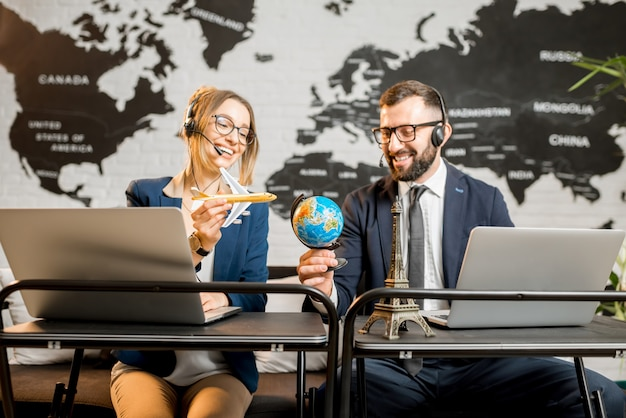 Coppia di travel manager che giocano con il globo e l'aereo seduti nell'ufficio dell'agenzia con la mappa del mondo sullo sfondo