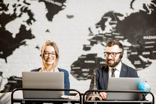 Coppia di travel manager che lavorano online con laptop e cuffie presso l'ufficio dell'agenzia con mappa del mondo sullo sfondo