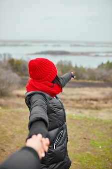 Coppia di viaggiatori che si tengono per mano al paesaggio fluviale nebbioso