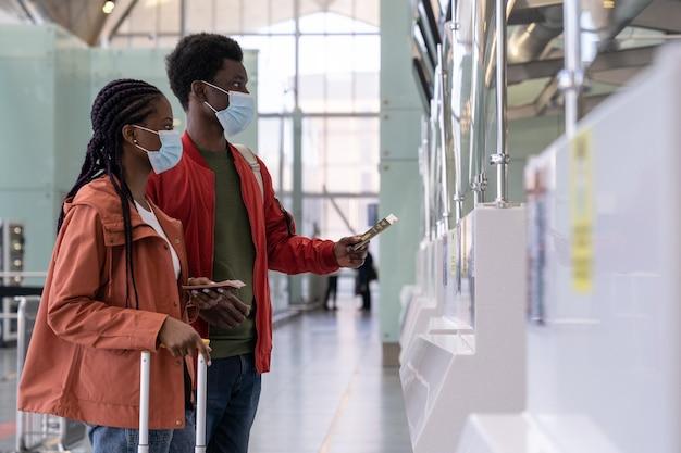 Coppia di viaggiatori in maschera al banco del check-in in aeroporto prima del volo durante l'epidemia di coronavirus
