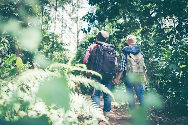 Coppia i viaggiatori con gli zainhi che si rilassano nella giungla di verdi