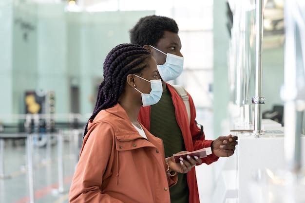 Coppia di viaggiatori con maschera facciale al banco del check-in in aeroporto prima del volo