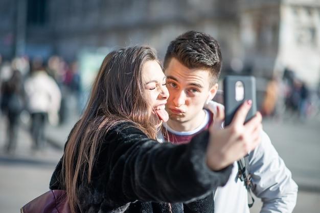 Coppia di turisti che si scattano un selfie nella città di milano, italia