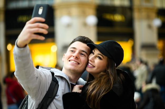 Coppia di turisti che prendono un selfie in città