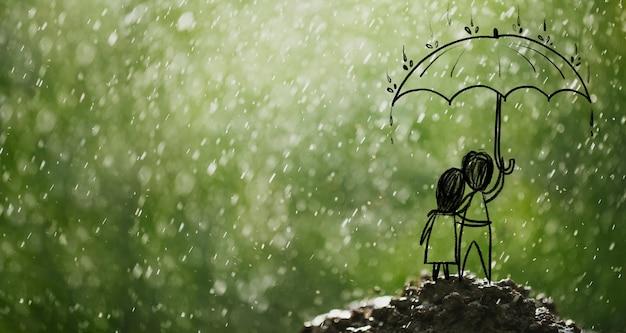 Coppia voltando le spalle tenendo un ombrello su un tumulo sotto la pioggia