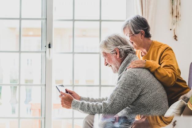 Coppia di due anziani allegri e felici maturi e anziani che utilizzano tablet e si divertono seduti sul divano di casa insieme. pensionati in pensione di bellezza che usano internet e navigano in rete