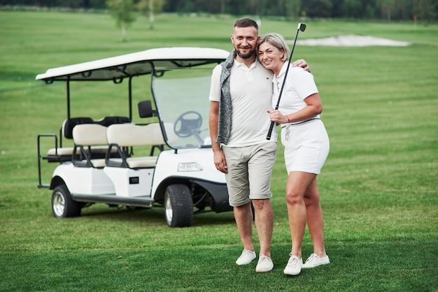 Coppia di due giocatori di golf che soggiornano sul prato verde con il carrello dietro di loro.