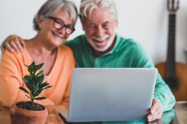 Coppia di due persone mature e anziane felici o anziani a casa seduti sul divano che si divertono e si divertono insieme guardando e usando un laptop o un computer pc