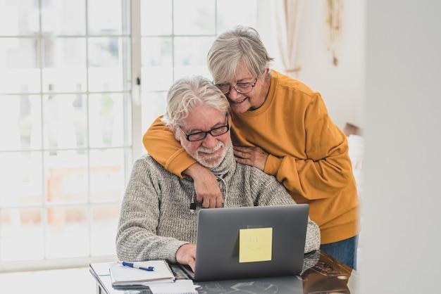 Coppia di due anziani felici che lavorano e usano il laptop insieme a casa sorridendo e divertendosi insieme - stile di vita di blocco