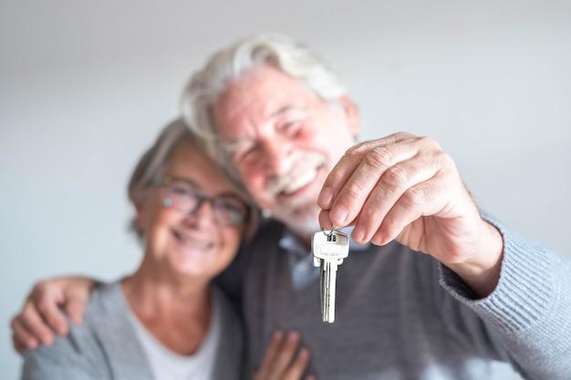 Un paio di due anziani dopo aver comprato una nuova casa o un'auto e andare a vivere insieme - uomo con una chiave e uomo maturo e donna che lo guardano