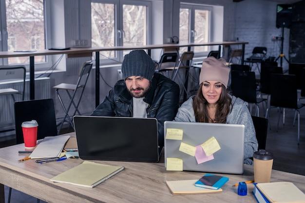 Coppia di studenti universitari hipster che studiano insieme ai laptop in aula magna