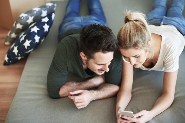 Coppia che usa il cellulare nella loro nuova casa