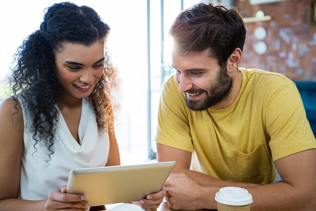 Coppie facendo uso di una compressa digitale nella caffetteria