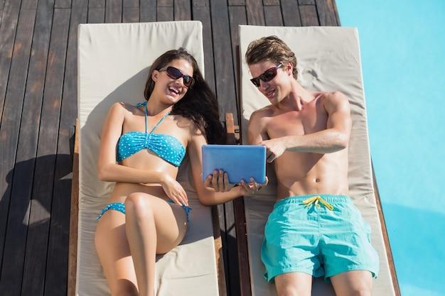 Coppie che per mezzo della compressa digitale sui lettini da piscina
