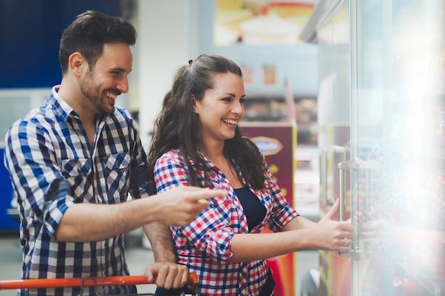 Coppia che utilizza il carrello della spesa in negozio per cibo e ingredienti