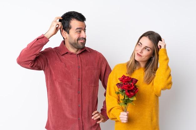 Le coppie nella tenuta di valentine day fioriscono sopra la parete isolata che ha dubbi mentre graffiano la testa