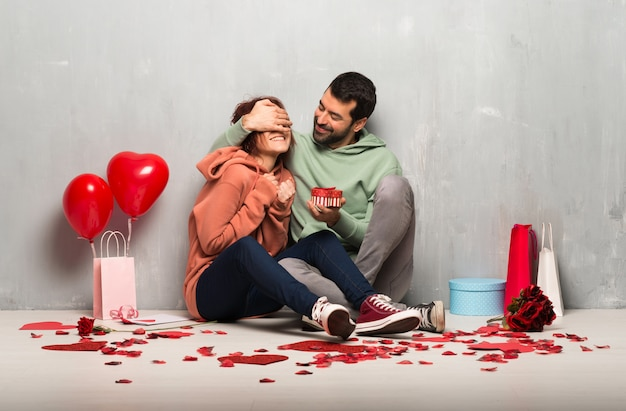 Coppie nel contenitore di regalo della tenuta di giorno di s. valentino