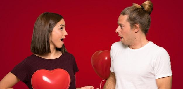Coppia nel giorno di san valentino con sorpresa e scioccato espressione facciale su sfondo rosso