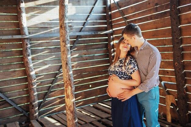 Tiro di foto aspettante del bambino delle coppie in una casa di legno