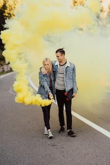 Coppia che cammina sulla strada in montagna che tiene fumo colorato giallo nelle mani.