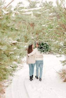 Coppie che camminano nel bosco innevato