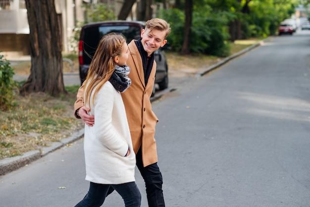 Coppia che cammina per strada abbracciandosi insieme. tempo libero e passatempo per gli amanti della gioventù degli appuntamenti casuali