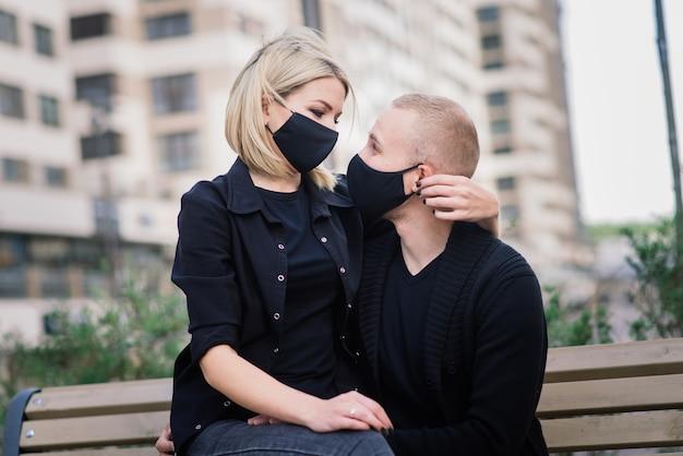 Coppie che indossano maschere protettive alla moda, camminando in una strada vuota della città durante la quarantena