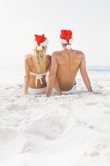 Coppia che indossa il cappello della santa sulla spiaggia