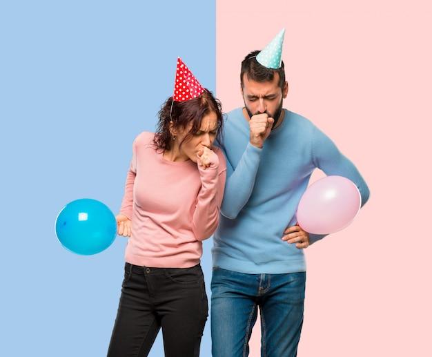 Coppia con palloncini e cappelli di compleanno soffre di tosse e si sente male