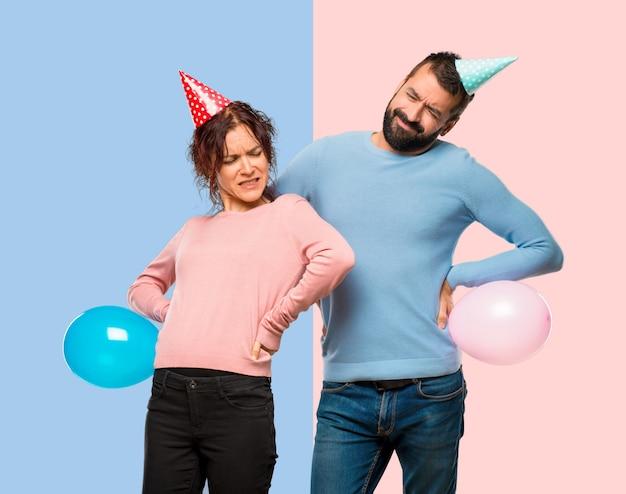 Coppia con palloncini e cappelli di compleanno che soffrono di mal di schiena per aver fatto uno sforzo