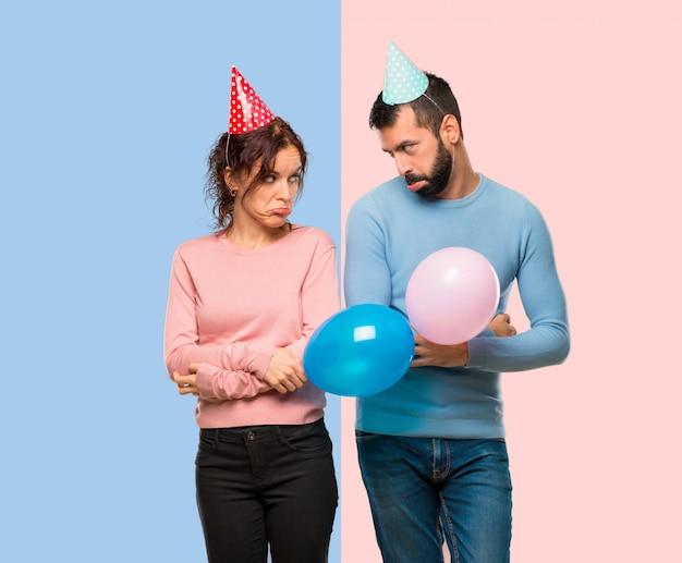 Coppia con palloncini e cappelli di compleanno con espressione triste e depresso.