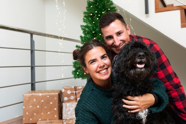 Coppia con cane barboncino nero guardando la fotocamera albero di natale e presente in background holiday