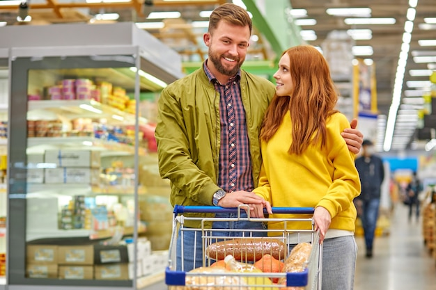 Coppia con carrello pieno di cibo nel negozio di alimentari, acquisto di pasti per la casa, signora dai capelli rossi guarda il marito con amore, sorriso