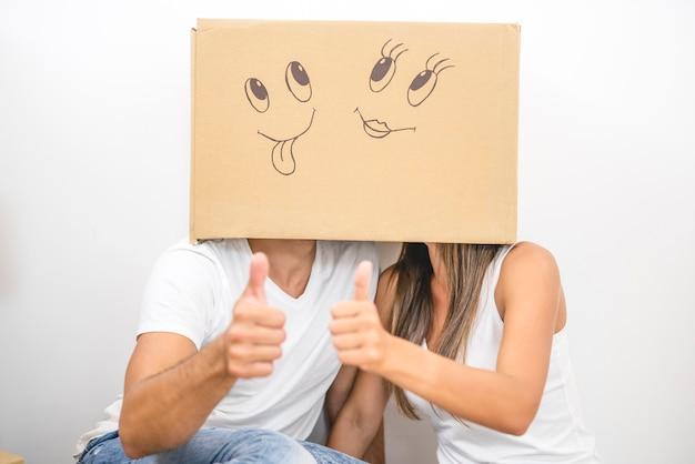 La coppia con una scatola di cartone sulla testa pollice in su