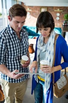 Coppia con tazze di caffè utilizzando una tavoletta digitale