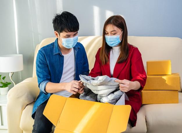 Coppia con maschera facciale che apre una cassetta dei pacchi di cartone a casa durante la pandemia di coronavirus